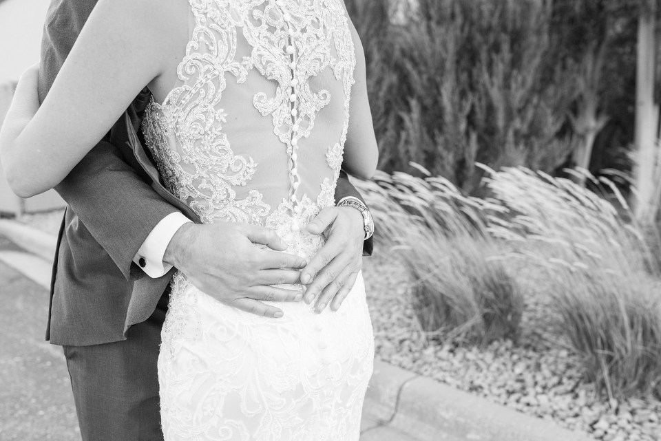 A groom's hands rest on his bride's back during their first look in black and white