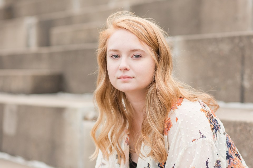 Senior girl with fair red hair stares into the camera
