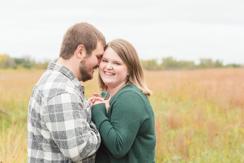 A couple smile and holds hands during their engagement session at Buffalo River State Park