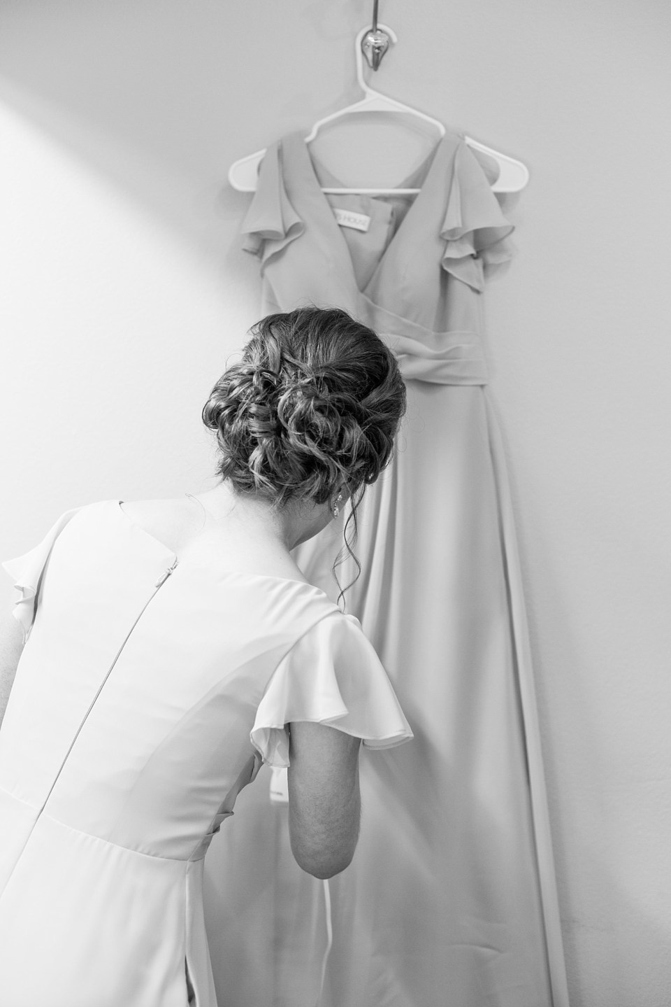 A Bridesmaid steams her dress at the beginning of the wedding timeline