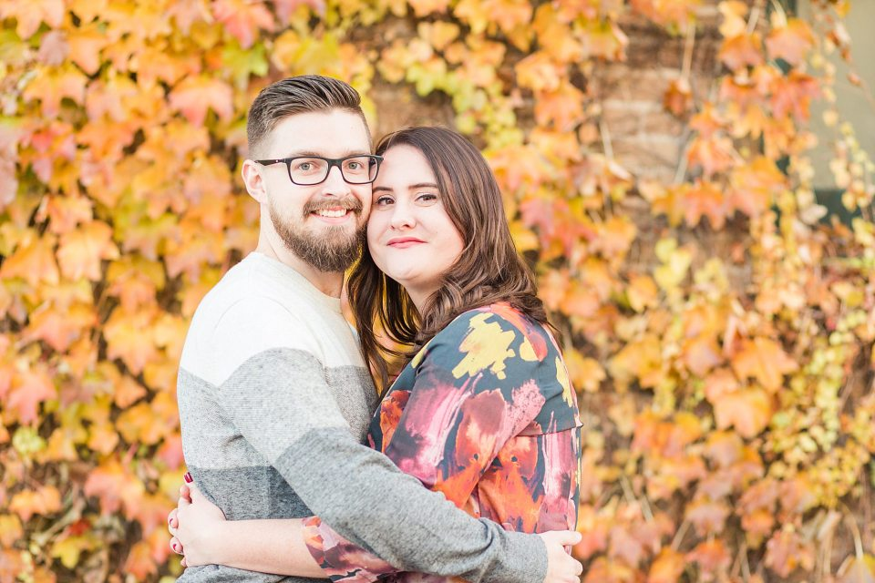 Orange fall leaves behind a couple pop during this colorful fall engagement session