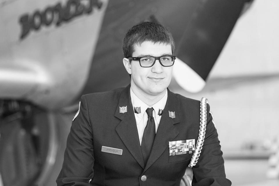 A high school senior in his JROTC uniform smiles at the Fargo Air Museum