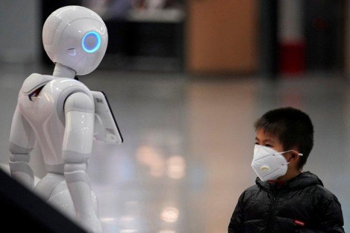 Seorang anak lelaki memperhatikan robot sambil memakai masker di Bandara Internasional Pudong di Shanghai, China, Senin (27/1/2020). (REUTERS/ALY SONG)