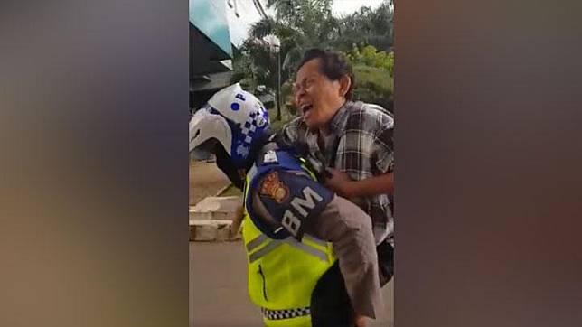 Seorang anggota polisi menggendong penumpang Transjakarta yang diduga terkena serangan jantung di halte depan RS Harapan Kita.