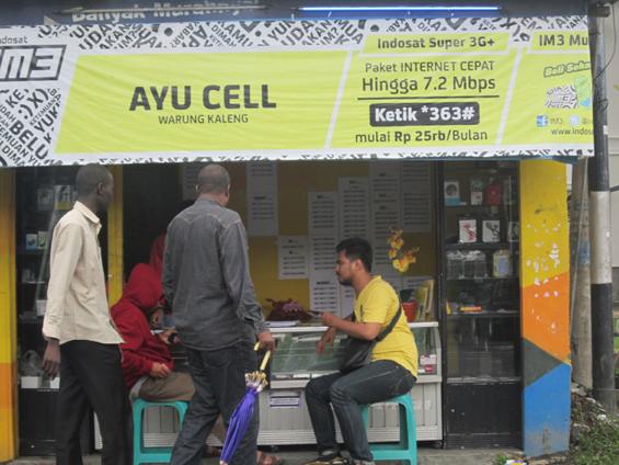 Pijar (baju kuning), partisipan dari Komunitas Kinetik, Surabaya, ketika sedang melakukan wawancara kepada penjaga kios ponsel di sekitar Kampung Arab.