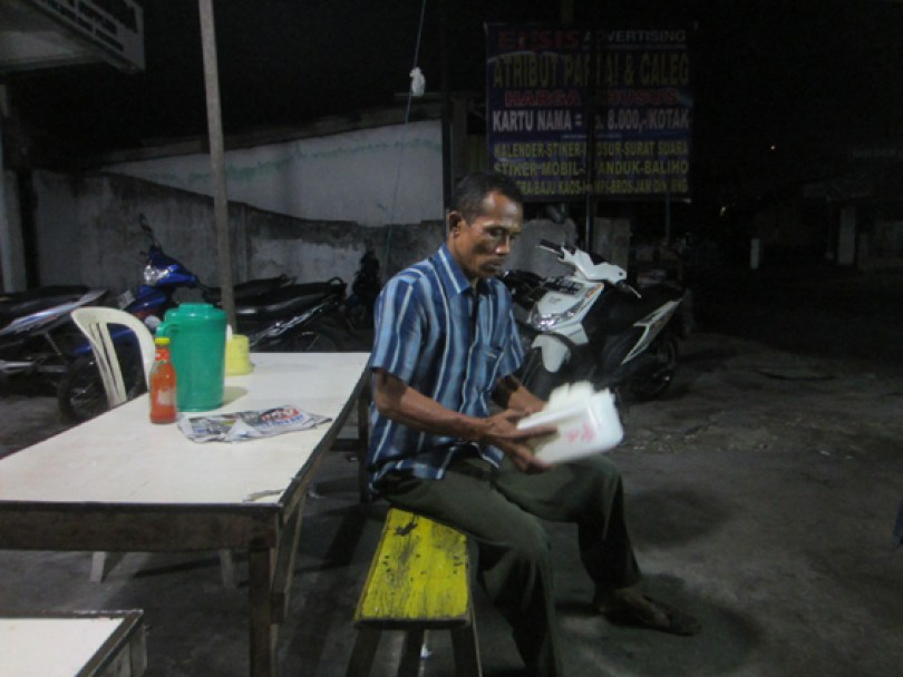 Pak Jon sedang mengeringkan nasi yang baru dimasak agar mudah dibuat menjadi nasi goreng.