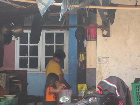 Mbak Minah dan anaknya sedang memasak di warung miliknya.