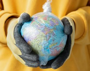 Hands in yellow and black gloves holding a model of the Earth wrapped in a plastic bag against a bright yellow sweater