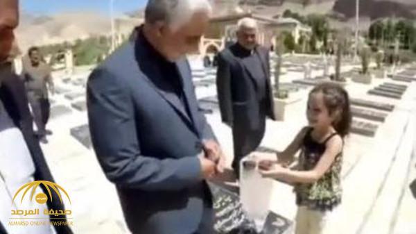 """لم يعد يأمن على نفسه من أحد.. شاهد ردة فعل """"سليماني"""" حينما قدمت له طفلة شوكولاتة وهو يتجول في مقبرة بإيران!"""