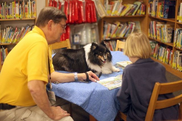 Cooper, the therapy dog, and his partner Lee engage in a literacy program – Sit, Stay, Read – at Hall Kent Elementary School.