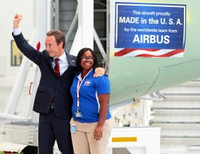 Fabrice Bregier, Airbus President and CEO, left, and Airbus employee Chandra Smith of Mobile, Ala., celebrate after placing a banner on an airplane part at the conclusion of the grand opening ceremony of Airbus U.S. Manufacturing Facility on Monday, Sept. 14, 2015, in Mobile. (Mike Kittrell/Alabama NewsCenter)
