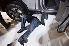 A member of the media lays under a 2017 Honda Motor Co. Ridgeline after the debut at the 2016 North American International Auto Show. (Daniel Acker/Bloomberg)