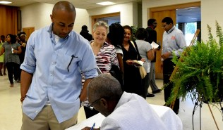 Roderick Royal signs copies of his book. (Solomon Crenshaw Jr./Alabama NewsCenter)