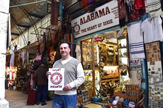 """University of Alabama alumnus Hani Imam outside his Jerusalem shop, """"Alabama -- The Heart of Dixie."""" (Karim Shamsi-Basha/Alabama NewsCenter)"""