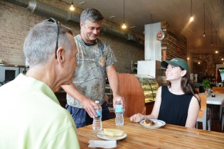 Seaborn Whatley serves water to Iander and Becky Allen at Pie Lab. (Karim Shamsi-Basha / Alabama NewsCenter)