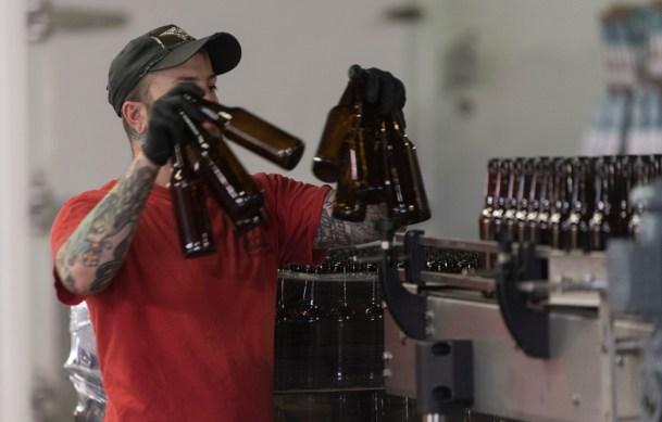 Daniel Beeler loads empty bottles on the bottling line at the Back Forty Beer Co. in Gadsden. (Bernard Troncale / Alabama NewsCenter)