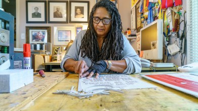 Debra Riffe carves her design into a piece of artist-grade linoleum. (Mark Sandlin/Alabama NewsCenter)