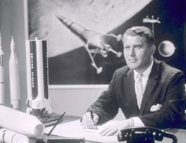 Dr. Wernher von Braun is in his office, with an artist's concept of a lunar lander in background and models of Mercury-Redstone, Juno, and Saturn I. (NASA, Wikimedia)