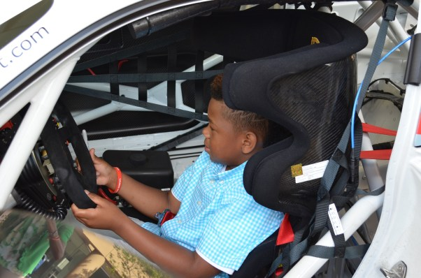 Trevor Moultrie, a survivor of childhood cancer, sits in the driver's seat of the new Racing for Children's Indy Car. (Michael Tomberlin/Alabama NewsCenter)