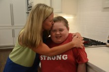 Melissa Goldsmith squeezes and kisses her son Fuller Goldsmith in the kitchen. (Karim Shamsi-Basha / Alabama NewsCenter)