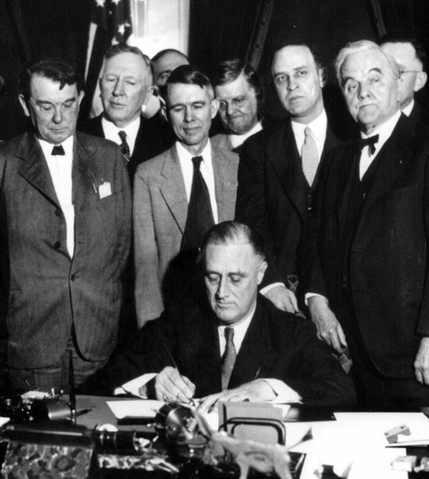 U.S. President Franklin D. Roosevelt signs the TVA Act, which established the Tennessee Valley Authority. Sen. George Norris, who sponsored the act, is on the far right. (Tennessee Valley Authority, Wikimedia)