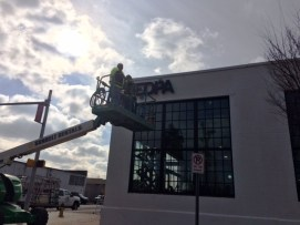 A worker installs the EDPA sign on the new downtown Birmingham headquarters earlier this year. (Michael Tomberlin / Alabama NewsCenter)