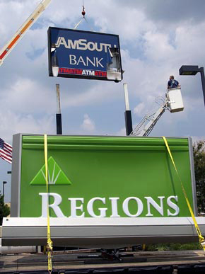 An AmSouth Bank sign is replaced with a Regions sign after the two banks merged and the AmSouth name was retired. (From Encyclopedia of Alabama, Courtesy of The Huntsville Times)
