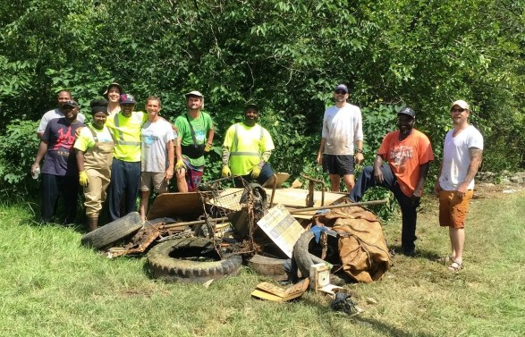 Workers display the pile of trash they removed from Valley Creek in Midfield. Volunteers and public works crews working from seven locations removed tons of debris in this year's cleanup. (Jefferson County Department of Public Health)
