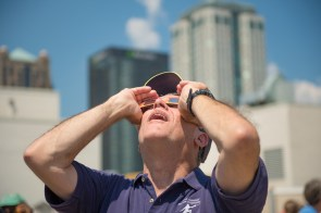 Volunteer, former college professor Bruce Bizzoco watches the solar eclipse at McWane Science Center. (Phil Free / Alabama NewsCenter)