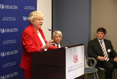Alabama Governor Kay Ivy speaks during a press conference at USA Medical Center as USA President Tony Waldrop, center, and USA Medical Center Administrator Sam Dean listen. (University of South Alabama)