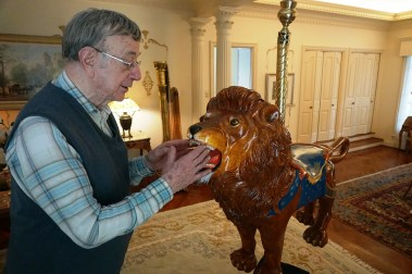 Pappas examines his wood-carving handiwork on this carousel lion. (Erin Harney/Alabama NewsCenter)
