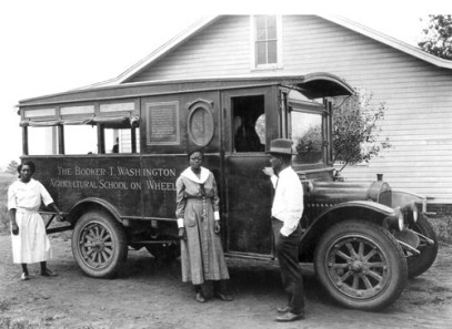 """Tuskegee agricultural science pioneer George Washington Carver developed the """"Movable School,"""" a wagon and later a truck that brought new tools and crops to farmers who could not travel to Tuskegee for instruction. The staff of three included, from left, a home agent, a registered nurse and a farm demonstration agent. (From Encyclopedia of Alabama, courtesy of the National Archives and Records Administration)"""