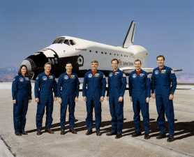 These seven NASA astronauts are currently training for the first flight of Endeavour, Orbiter Vehicle (OV) 105, seen in the background. Crewmembers, wearing navy blue flight suits, are (left to right) Mission Specialist (MS) Kathryn C. Thornton, MS Bruce E. Melnick, MS Pierre J. Thuot, Commander Daniel C. Brandenstein, Pilot Kevin P. Chilton, MS Thomas D. Akers, and MS Richard J. Hieb. (Photograph by NASA JSC contract photographer Mark Sowa, NASA, Wikipedia)