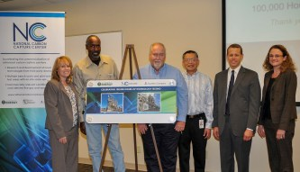 From left, employees Michele Corser, James Woods, David Mims and Tony Wu accept a commemorative graphic from Alabama Power Senior Production Officer Jim Heilbron and Roxann Walsh, director of reduced-carbon, renewable and distributed energy R&D. (Billy Brown)