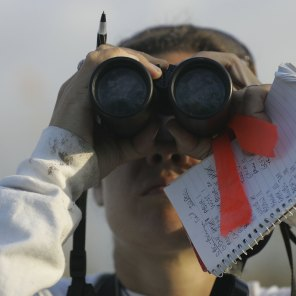 Bird counter Mandy Holmgren holds a tally sheet of spotted birds as she looks for more through binoculars while participating in the Audubon Societies Christmas Bird Count December 20, 2006 in the Florida Everglades National Park. (Photo by Joe Raedle/Getty Images)