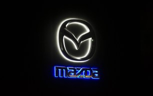The Mazda Motor Corp. logo is illuminated at the launch of the company's Roadster RF vehicle in Tokyo, Japan, on Thursday, Nov. 10, 2016. Mazda unveiled the sports car known as MX-5 RF outside Japan to the Japanese market today. Mazda has been developing electric vehicle on its own and now is in talks to proceed in joint effort with Toyota, President Masamichi Kogai tells reporters in Tokyo. Photographer: Tomohiro Ohsumi/Bloomberg