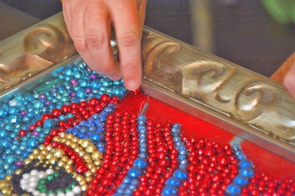 Kathleen McCarron painstakingly glues Mardi Gras beads over her original painting of a Mardi Gras mask. (Karim Shamsi-Basha / Alabama NewsCenter)