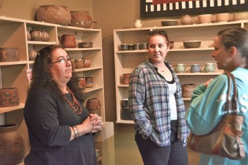 Guadalupe Lanning Robinson talks with customers about her Aztec-inspired pottery at Guadalupe Pots in Huntsville. (Karim Shamsi-Basha / Alabama NewsCenter)