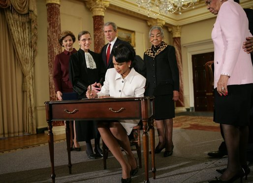Secretary of State Dr. Condoleezza Rice signs official papers Friday, Jan. 28, 2005, after receiving the oath of office during her ceremonial swearing in at the Department of State. Watching on are, from left, Laura Bush, Justice Ruth Bader Ginsburg, President George W. Bush and an unidentified family member. (White House photo by Eric Draper, Wikipedia)