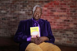 "Brown holds one of his most prized possessions, his book ""Pure Butter."" (Bruce Nix/Alabama NewsCenter)"