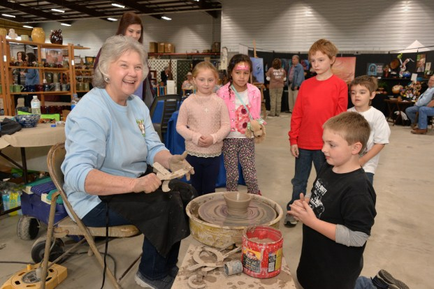 Sandra Brown, widow of Jerry Brown, continuing the family pottery tradition at last year's festival by demonstrating for a group of young art enthusiasts. (Michael E. Palmer)