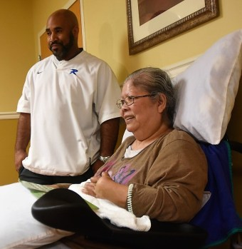 Ramsay coach Ronnie Jackson looks on as his team members play bingo with residents at South Rehabilitation and Health. (Solomon Crenshaw Jr. / Alabama NewsCenter)