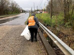 A volunteer picks up littler along Valley Creek in Jefferson County. (Michael Sznajderman/Alabama NewsCenter)