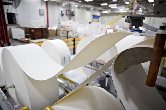 Rolls of paper pulp are fed into a machine during production at a Kimberly-Clark Corp. facility. (Daniel Acker/Bloomberg)