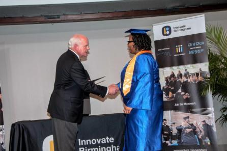 UAB President Ray Watts presents Innovate Birmingham Development Program graduates with their certificates. Many of them already have jobs waiting for them. (Billy Brown / Alabama NewsCenter)
