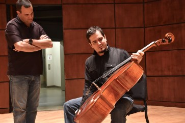 Avshi Weinstein shows a cello to ASO Conductor Carlos Izcaray. (Karim Shamsi-Basha/Alabama NewsCenter)