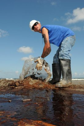 A worker cleans up oily waste on Elmer's Island just west of Grand Isle, Louisiana, May 21, 2010. (PO3 Patrick Kelley, Wikipedia)