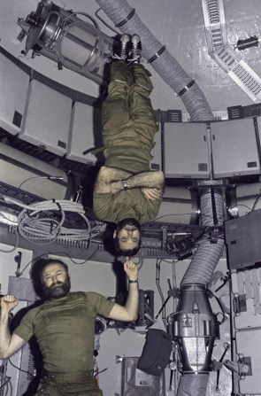 Skylab 4 commander Gerald Carr jokingly demonstrates weight training in zero gravity as he balances fellow astronaut William Pogue, the mission's pilot, upside down on his finger. Skylab was America's first space station and orbital science and engineering laboratory. The station was launched into Earth orbit by a Saturn V rocket on May 14, 1973, as a followup to the Apollo program. Three crews visited the station, with their missions lasting 28, 59 and 84 days, respectively. (NASA)