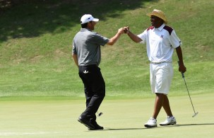 Alabama A&M head football Coach Connell Maynor gets a fist bump for holing a putt at the Regions Tradition Pro Am. (Solomon Crenshaw/Alabama NewsCenter)