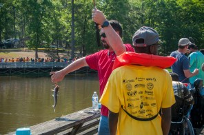 Volunteers from Alabama Power lend a hand after students make a catch. (Billy Brown/Alabama NewsCenter)